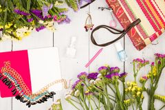 bolso de la paja, flores coloridas, libreta, maquillaje de los cosméticos, joya y esencial en el fondo de madera blanco Imagen de archivo