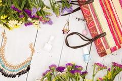 bolso de la paja, flores coloridas, maquillaje de los cosméticos, joya y esencial en el fondo de madera blanco Imagenes de archivo
