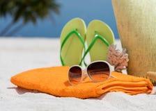 Bolso de la playa del verano con el coral, la toalla, las gafas de sol y las chancletas Imagen de archivo libre de regalías