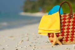 Bolso de la playa del verano con la cáscara, toalla en la playa arenosa Imágenes de archivo libres de regalías
