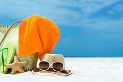 Bolso de la playa del verano con las estrellas de mar, la toalla, las gafas de sol y las chancletas en la playa arenosa Imagenes de archivo