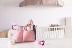 Bolso de maternidad con los accesorios del bebé en la tabla imagen de archivo