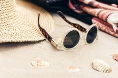 Bolso de mimbre de la playa de la paja del verano del vintage, vidrios de sol, sombrero, abrigo en la arena, fondo tropical de la fotos de archivo