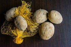 Bolso de Raschel con las patatas en la tabla fotografía de archivo libre de regalías