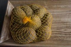 Bolso de Raschel con las patatas en la tabla fotos de archivo