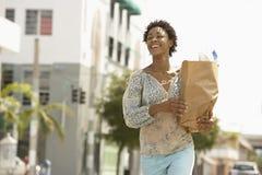 Bolso de ultramarinos de la mujer que lleva mientras que camina en la calle Imagen de archivo libre de regalías