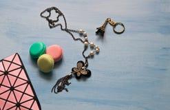 Bolso, decoración, llavero y macarrones cosméticos en fondo azul imagen de archivo libre de regalías