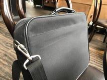 Bolso del brazo del ordenador portátil en una silla de madera Imagen de archivo