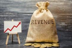 Bolso del dinero con los ingresos y el gráfico de la palabra para arriba El concepto de beneficios y de finanzas cada vez mayores imágenes de archivo libres de regalías