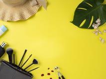 Bolso del maquillaje con la variedad de fondo amarillo de los productos de belleza imagen de archivo