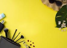 Bolso del maquillaje con la variedad de fondo amarillo de los productos de belleza foto de archivo