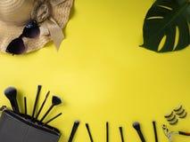 Bolso del maquillaje con la variedad de fondo amarillo de los productos de belleza imagenes de archivo