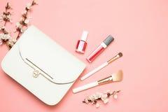 Bolso del maquillaje con los cosméticos aislados en fondo coralino de vida foto de archivo libre de regalías