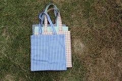 Bolso del paño del color y del modelo puesto en pila en hierba verde imágenes de archivo libres de regalías