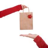 Bolso del papper de la explotación agrícola de la mano de la mujer con la cinta roja fotos de archivo libres de regalías