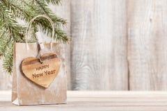 Bolso del regalo del Año Nuevo con la etiqueta en forma de corazón de madera Foto de archivo libre de regalías