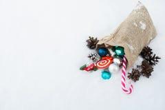 Bolso del regalo del ` s de Papá Noel por completo de los juguetes y de los regalos de la Navidad en la nieve Fotos de archivo libres de regalías