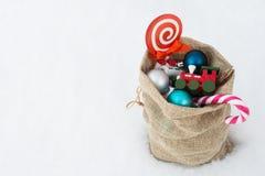 Bolso del regalo del ` s de Papá Noel por completo de los juguetes y de los regalos de la Navidad en la nieve Imágenes de archivo libres de regalías
