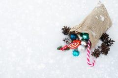 Bolso del regalo del ` s de Papá Noel por completo de los juguetes y de los regalos de la Navidad en la nieve Imagen de archivo libre de regalías