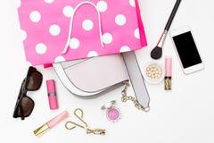 Bolso en un panier rosado y accesorios femeninos en un blanco Fotografía de archivo