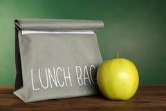 Bolso gris del almuerzo y manzana verde apetitosa en la tabla de madera Imagenes de archivo