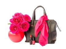 Bolso, lápiz labial, esmalte de uñas y rosas negros en el florero aislado Imágenes de archivo libres de regalías