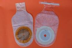 Bolso m?dico vac?o blanco de la operaci?n del intestino grueso dos en una tabla roja imágenes de archivo libres de regalías