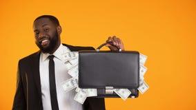 Bolso negro divertido de la tenencia del hombre de negocios con efectivo del dólar y pulgares-para arriba el mostrar almacen de metraje de vídeo