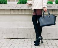 Bolso negro grande hermoso de moda en el brazo de la muchacha en un vestido gris de moda, presentando cerca de la pared en a Foto de archivo libre de regalías