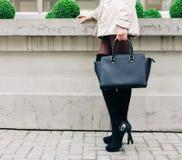 Bolso negro grande hermoso en el brazo de la muchacha morena zanquilarga increíble en un vestido gris de moda, presentando Fotografía de archivo