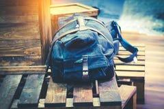 Bolso o mochila del viajero en la caja de madera Imagenes de archivo