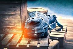 Bolso o mochila del viajero en la caja de madera Fotografía de archivo