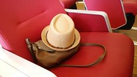 Bolso olvidado y un sombrero de paja del verano en el asiento fotografía de archivo libre de regalías