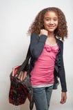 Bolso que lleva de la chica joven por completo de libros Imagen de archivo libre de regalías