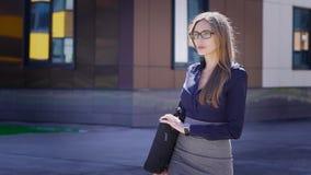 Bolso que lleva de la empresaria acertada Mujer joven confiada que sostiene el bolso y que camina en la calle en el edificio de o metrajes