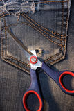 Bolso rasgado da sarja de Nimes com tesouras Fotografia de Stock Royalty Free