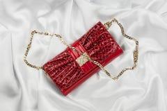Bolso rojo de la laca que miente en una seda blanca Imagen de archivo