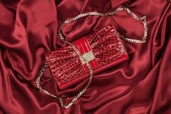 Bolso rojo de la laca que miente en una seda roja Imágenes de archivo libres de regalías