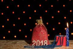Bolso rojo del Año Nuevo con un regalo, una vela azul y las gotas con el numbe Imagen de archivo