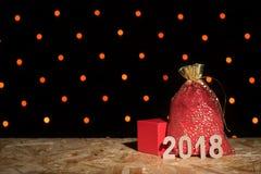 Bolso rojo del ` s del Año Nuevo con un regalo, una caja y los cuadros 2018 en un backgr Foto de archivo libre de regalías