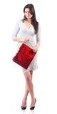 Bolso rojo que hace compras de la explotación agrícola de la mujer. Aislado Imagen de archivo libre de regalías
