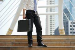 Bolso solo del documento del soporte del hombre de negocios que se sostiene en la escalera después de trabajar Imagenes de archivo