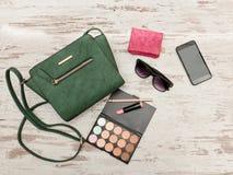Bolso, teléfono, paleta del sombreador de ojos, teléfono, gafas de sol y lápiz labial femeninos verdes en un fondo de madera Fotografía de archivo