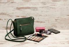 Bolso, teléfono, paleta del sombreador de ojos, teléfono, gafas de sol y lápiz labial femeninos verdes en un fondo de madera Fotos de archivo libres de regalías