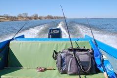 Bolso y cañas de pescar en el asiento trasero del barco de motor Imagenes de archivo