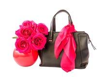 Bolso y rosas negros en el florero aislado Imagenes de archivo