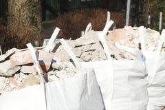 Bolsos de basura blancos con las piedras de los escombros Imagenes de archivo