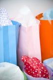 Bolsos de compras coloreados brillantes con el abrigo de regalo Fotografía de archivo libre de regalías