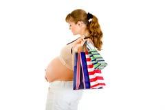 Bolsos de compras de la explotación agrícola de la mujer embarazada a disposición Foto de archivo