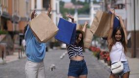 Bolsos de compras de levantamiento de las muchachas emocionadas para arriba en la calle metrajes